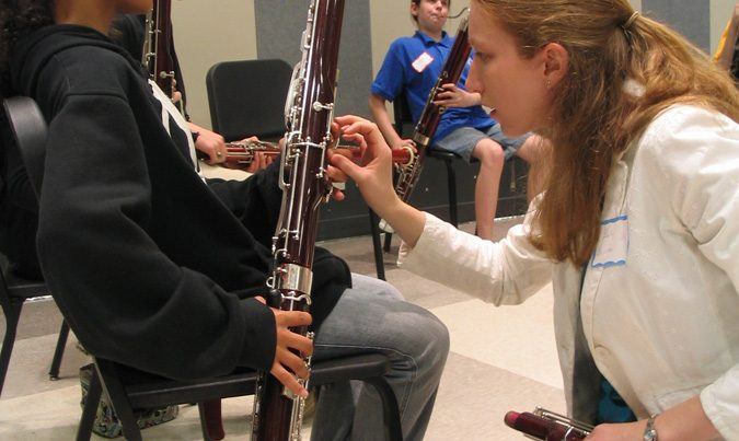 instructor fixing how student holds instrument