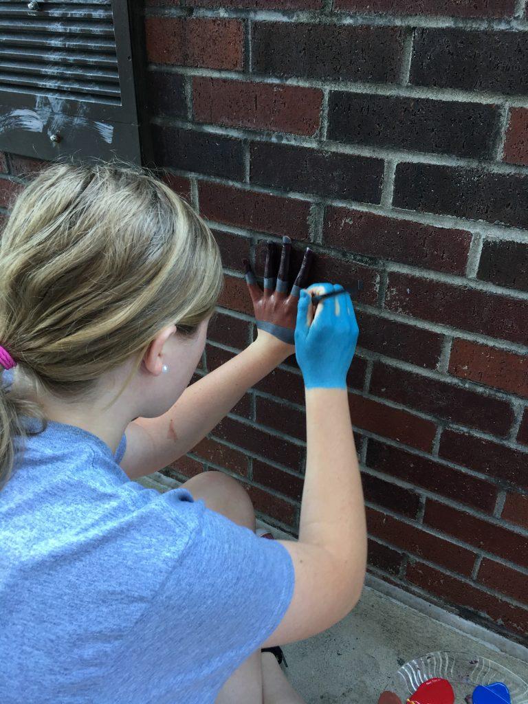 student artist painting hand