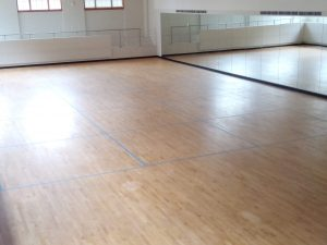 A photo of a dance studio with blue tape on the floor.