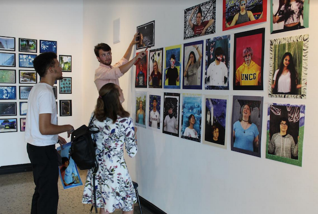 Students hanging pictures