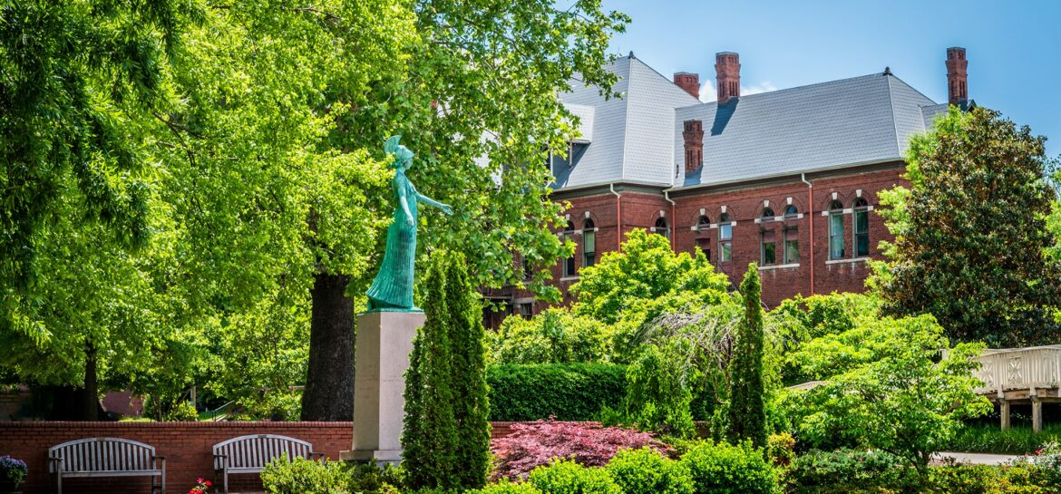 Minerva statue in full summer - green trees and roses blooming