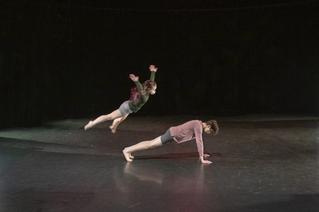 A dancer jumps over another dancer.