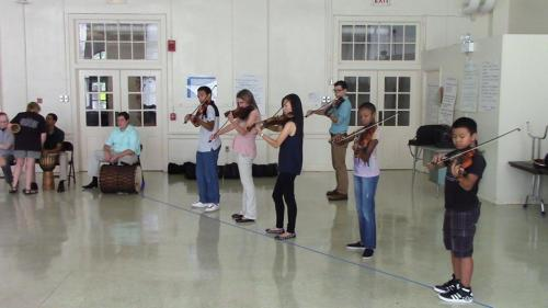 students performing on violins