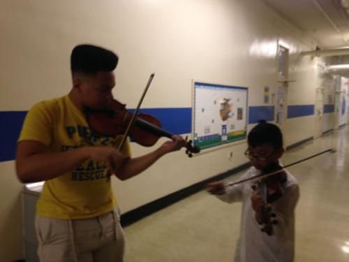 older student teaching younger student violin