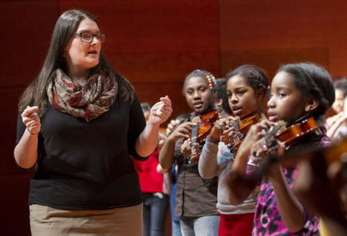 woman teaching students violin