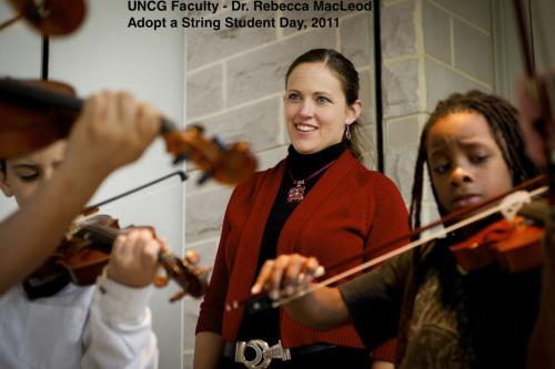 Dr. Rebecca MacLeod smiles as she looks at UNCG and Peck students playing together.
