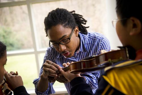 A UNCG student corrects a student's finger placement on his violin.