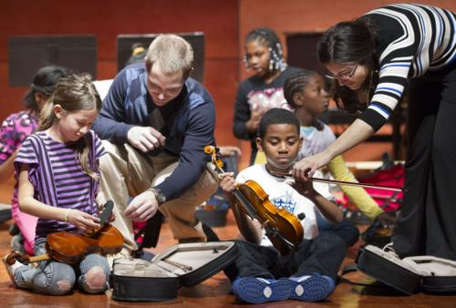 teachers helping students with instruments