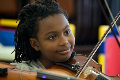 girl smiles as plays violin