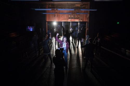 students onstage in dark with spotlight on one